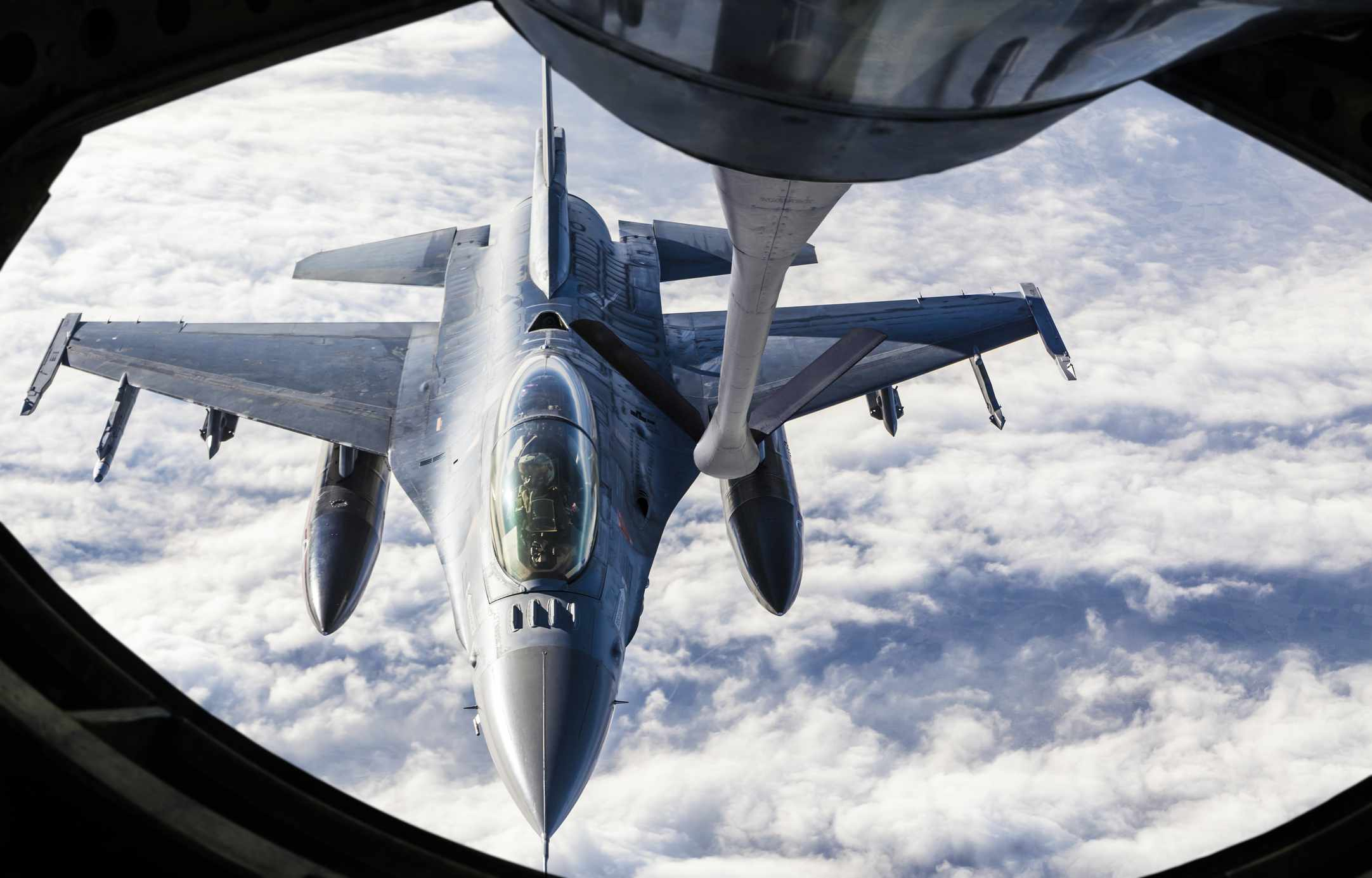 A fighter jet closing in on the refueling nozzle from a tanker in mid-air.