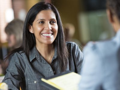 Hispanic woman with resume applying for job during interview meeting