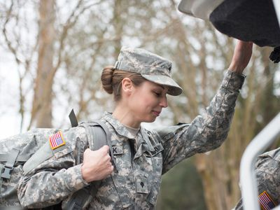 Female military officer putting her bags in the trunk of an SUV