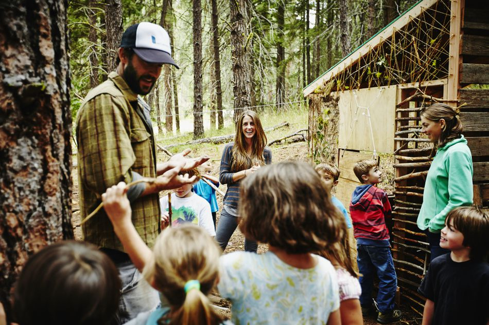 Camp counselors giving instructions to kids at a wooded summer camp.