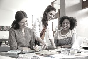 Happy female employees at work in office setting