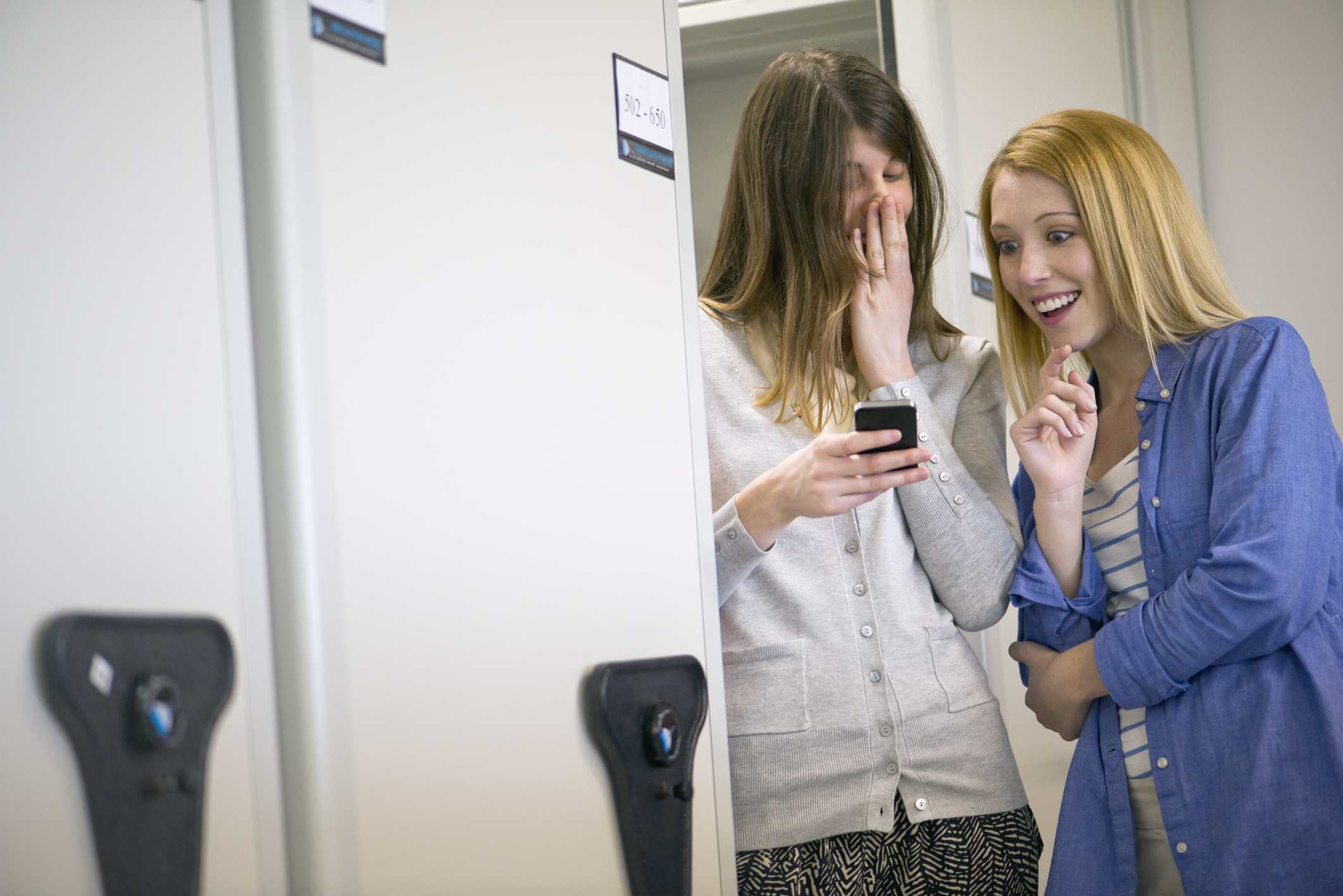 two women looking at phone and laughing