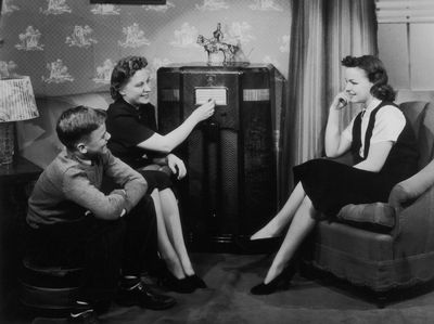 a vintage photo of a family listening to a radio together