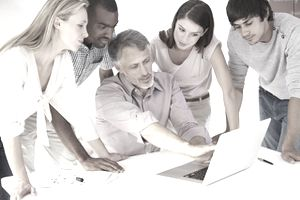 Group of employees listening to their team leader around a laptop