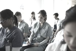 Nurse taking notes in seminar audience