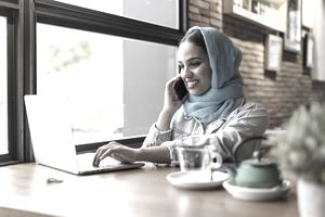 Businesswoman wearing turquoise hijab in a cafe and working with her laptop, on the phone