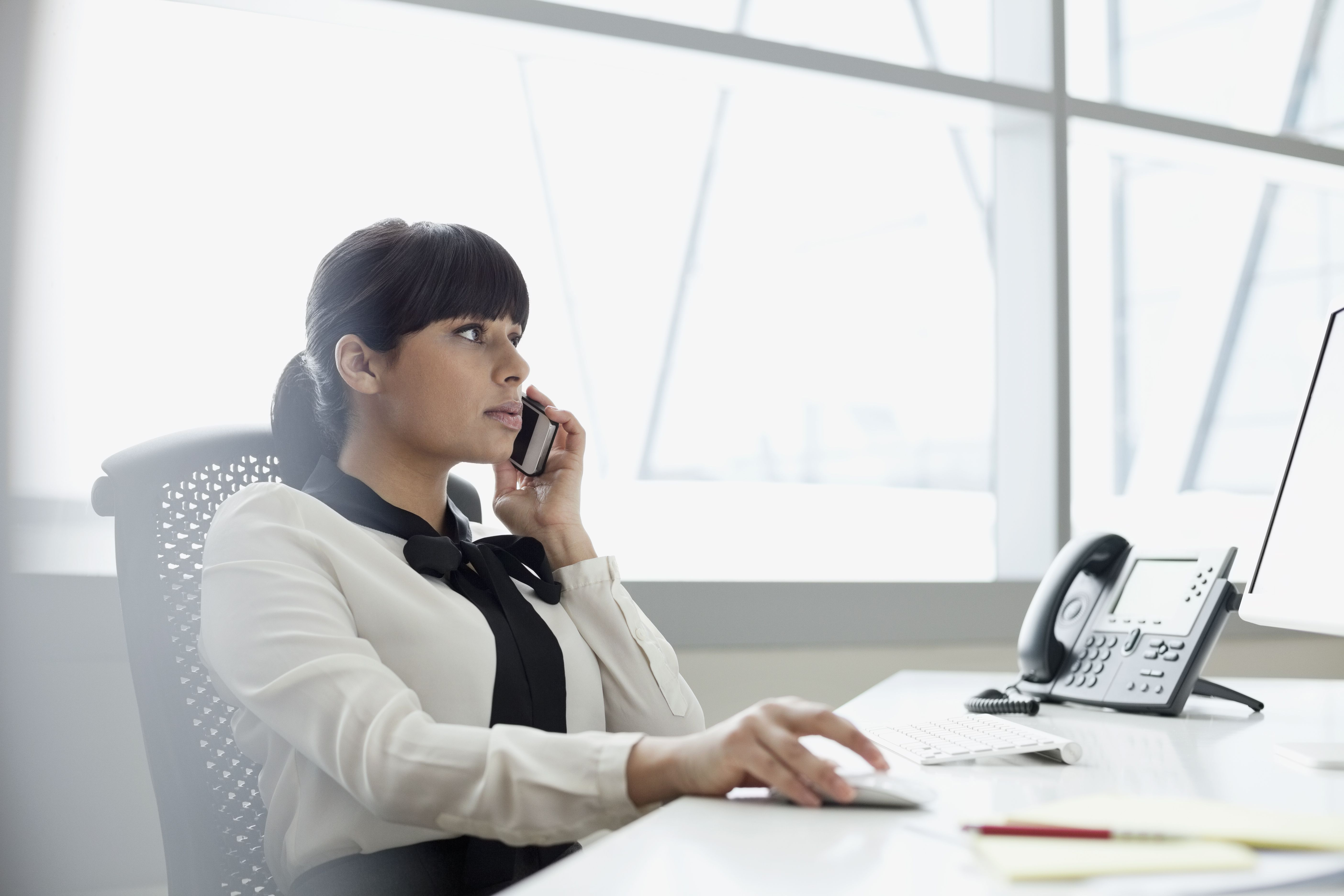 A businesswoman using mobile phone in office