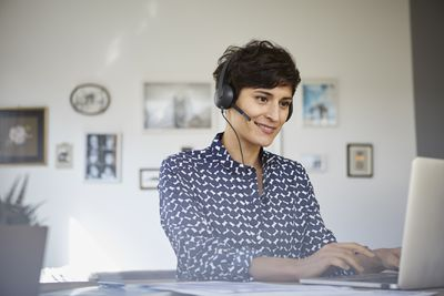 woman with light skin and short hair sits at a desk on a laptop. she is wearing a headset, perhaps for a conference call.