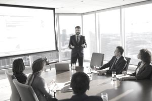 Financial advisor giving a presentation to institutional clients sitting around a conference room table.