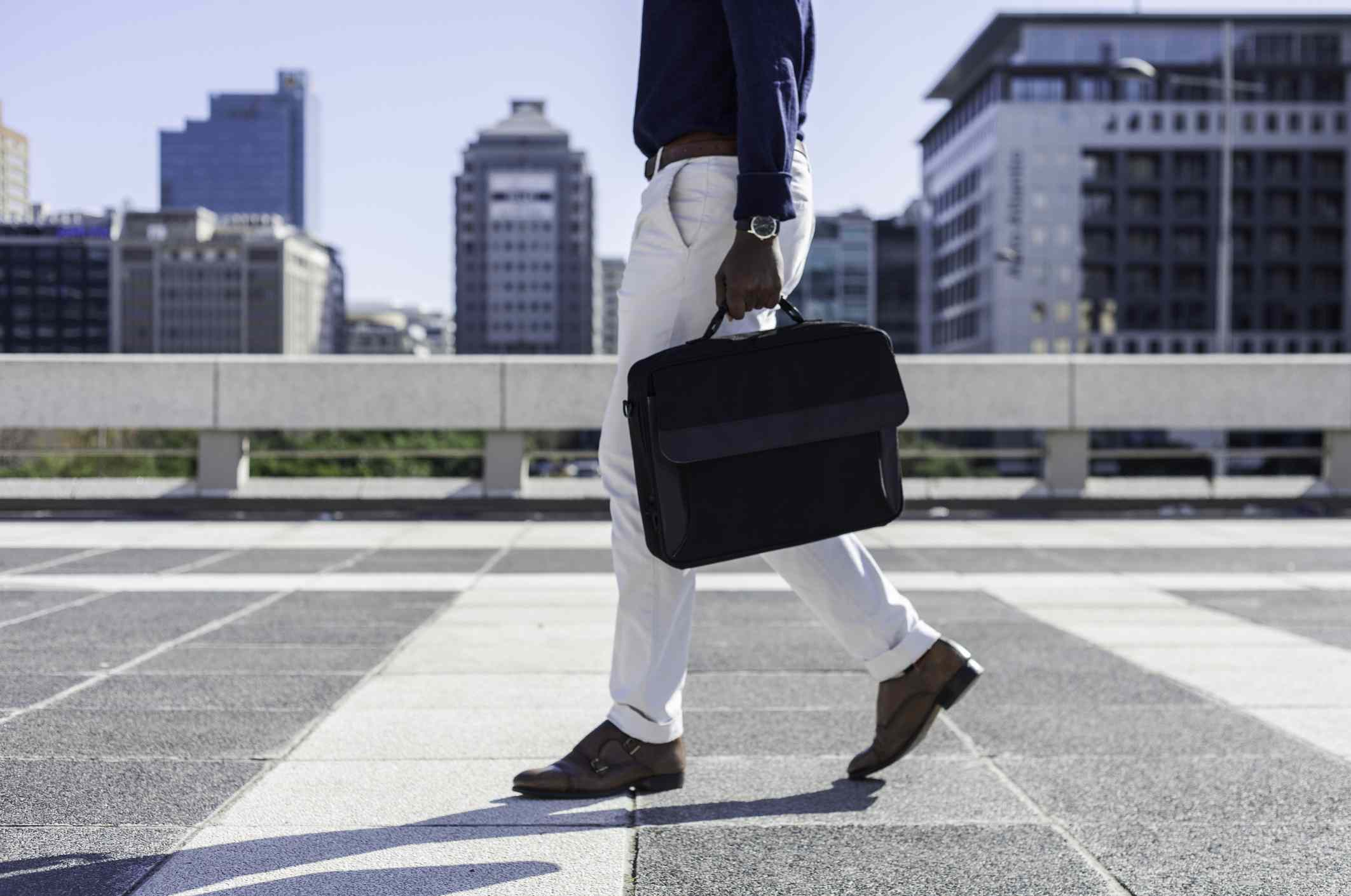 Business man walking down city sidewalk carrying a satchel bag on the way to an interview.