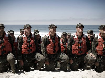 Military Apprentices kneeling on the beach.