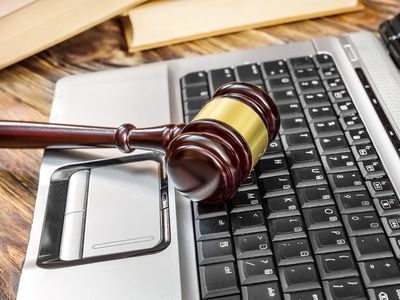 Judge's wooden gavel laying on a laptop