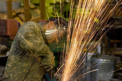 U.S. Army MOS 91E Allied Trade Specialist Brian Kilough, a metal worker, grinds stack of metal sheets using a circular grinder at Forward Operations Base Falcon, Baghdad, Iraq