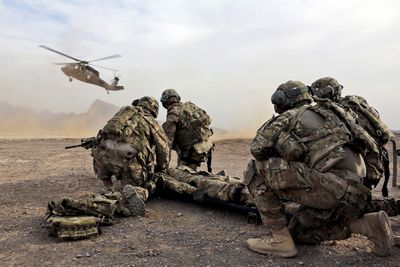 Soldiers surrounding wounded comrade waiting for rescue helicopter