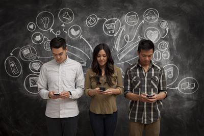 People on phones with social media icon chalkboard