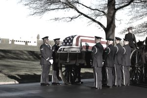 Soldiers carrying a coffin covered with a flag during a military funeral.