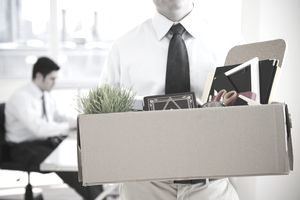Fired employee walking out of office with a box filled with supplies.