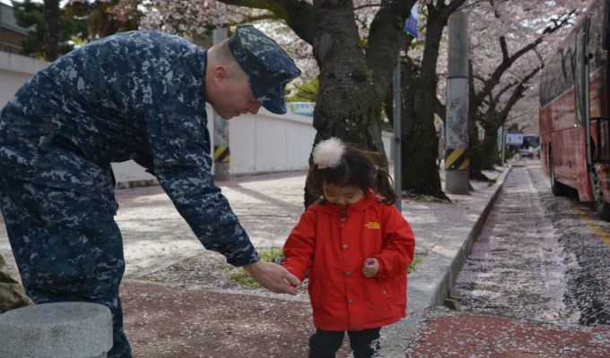 CFAC sailor offering candy to a local child during a parade at Chinhae.
