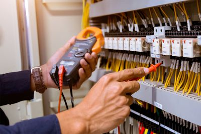 Electrician Measurements With Multimeter Testing Current Electric In Control Panel
