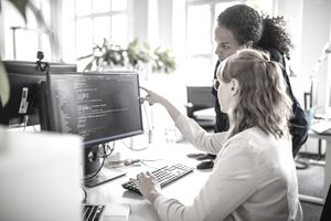 Women reviewing programming code together at a computer