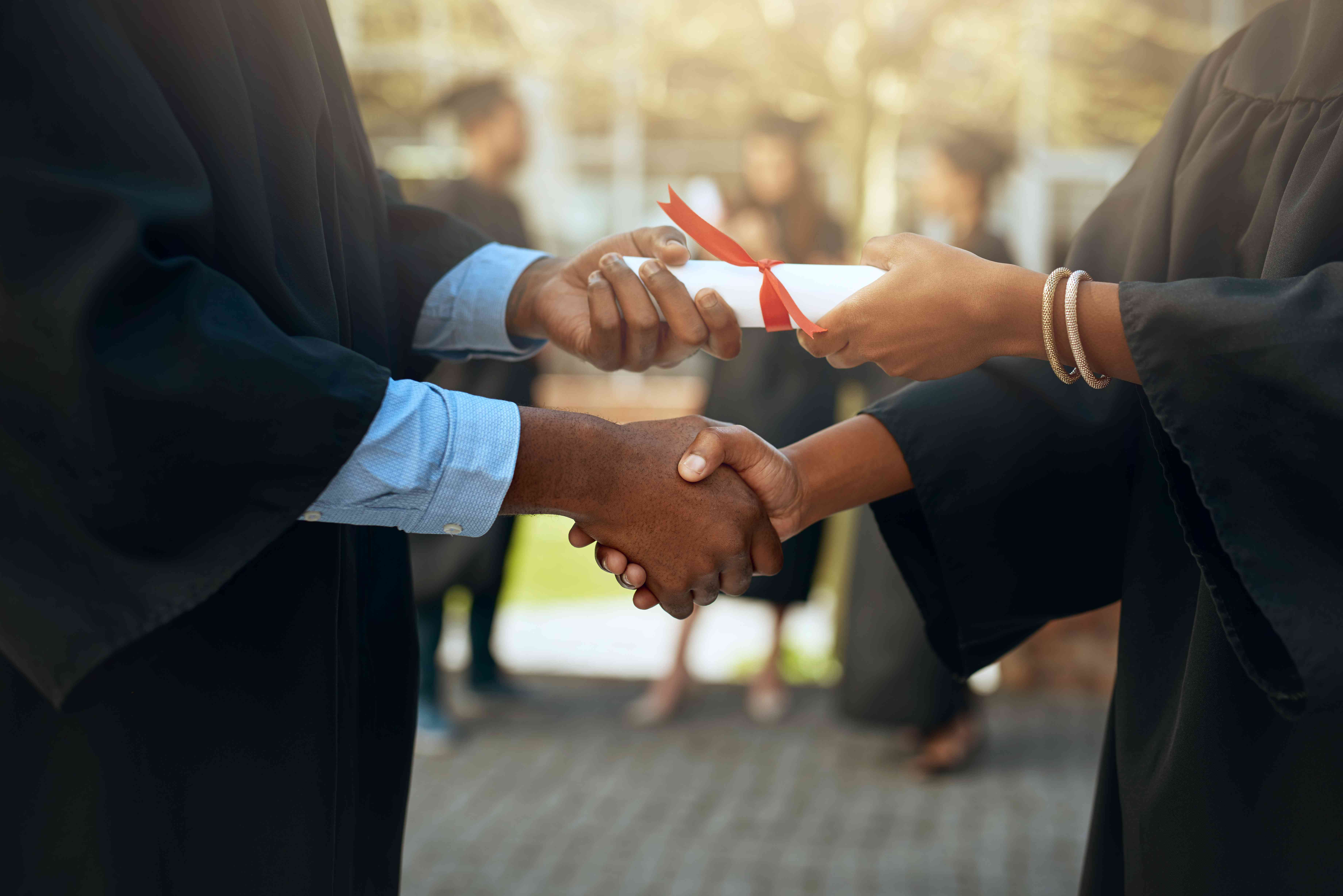 A graduate receiving a degree diploma and shaking hands