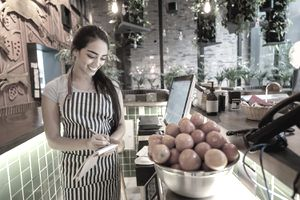Woman Working at a Restaurant Weighing Tomatoes in a Bowl Smiling