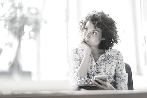 Businesswoman in office with smartphone and diary.