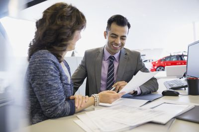 Advertising Sales Representative discussing a future ad with client at a car dealership.