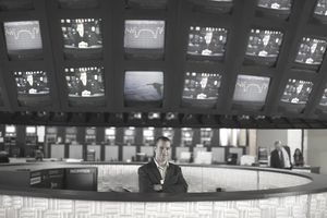 A photo of a man standing in a newsroom with TV monitors over his head.