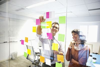 Co-workers brain storming with sticky notes on glass wall