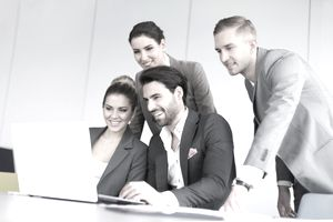group of business people smiling and looking at a computer