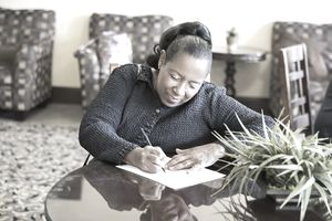 African American woman sitting at table completing paperwork