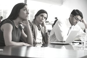 Bored and disgruntled team members looking away or distracted during a team meeting