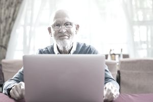 Confident senior man with laptop