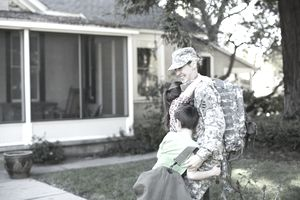 Soldier returning home getting a hug from children after being gone for training leave.