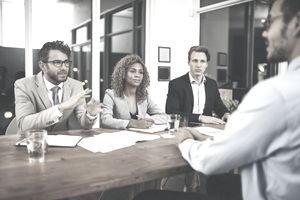 man interviewing with panel of three people