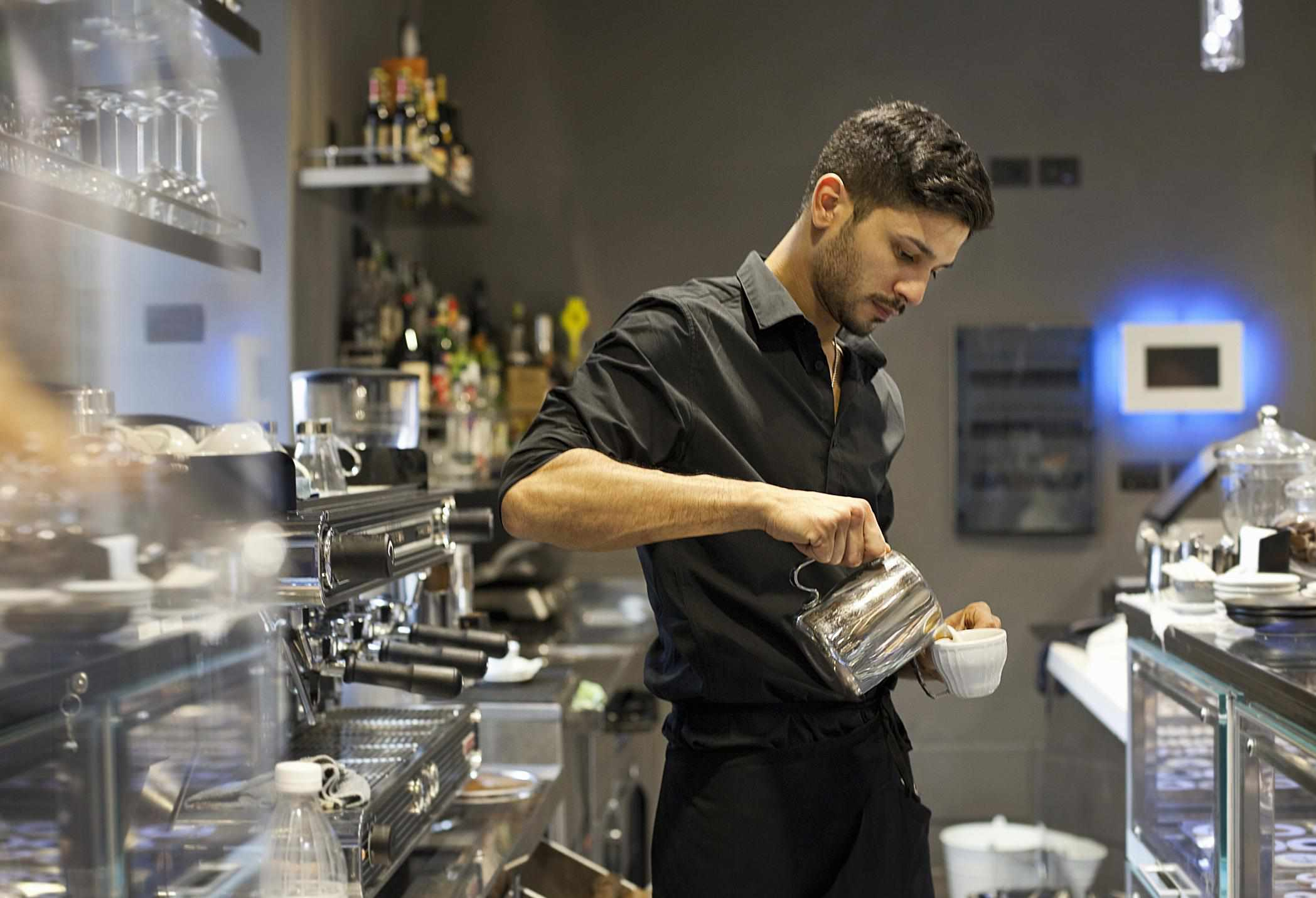 Barista pouring a latte at cafe