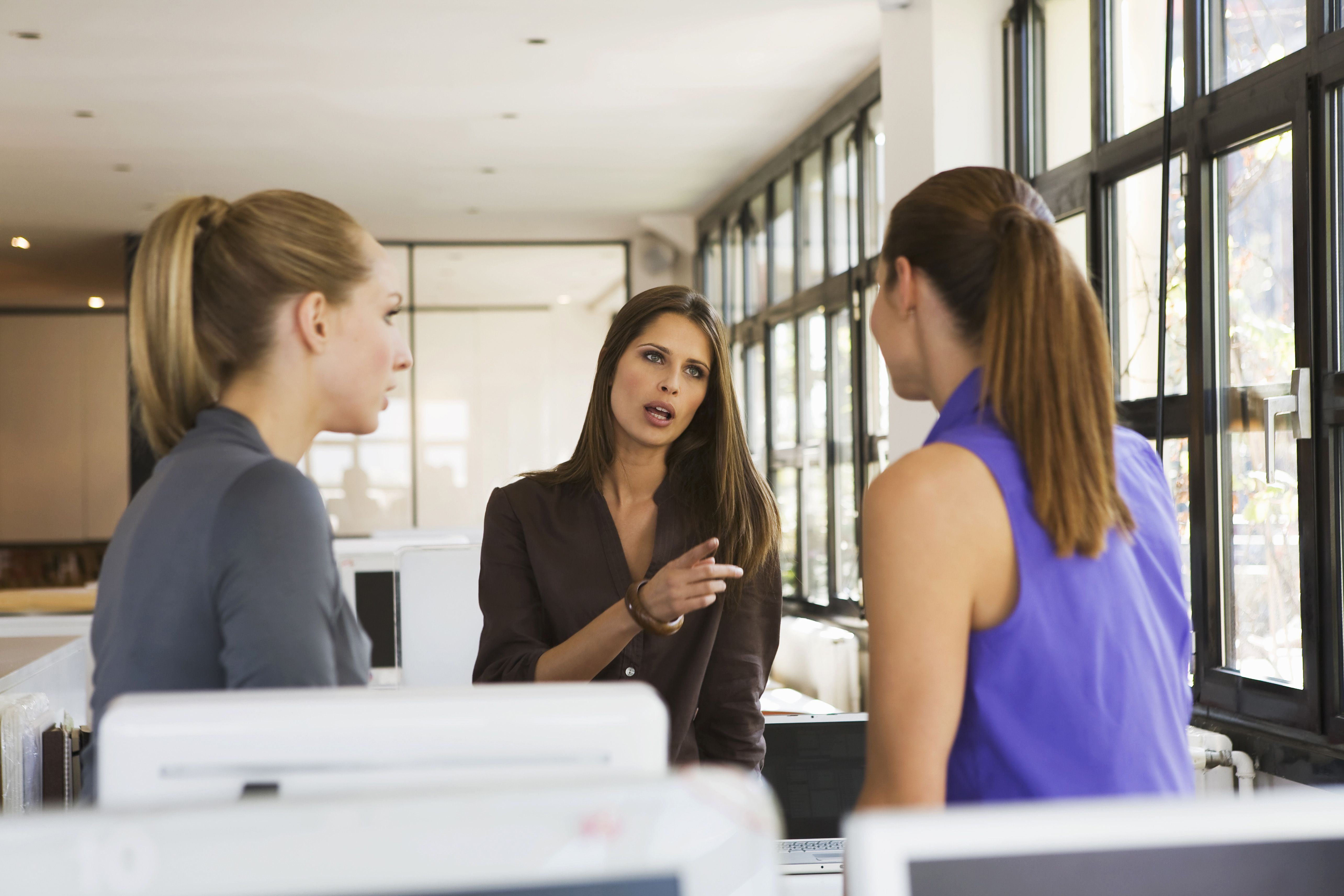 Three women in office having an argument that is causing negativity in their workplace.