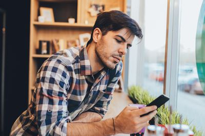 Man texting and job searching in cafe