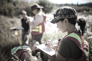 Environmental Science workers out in field, one woman documenting in a notebook