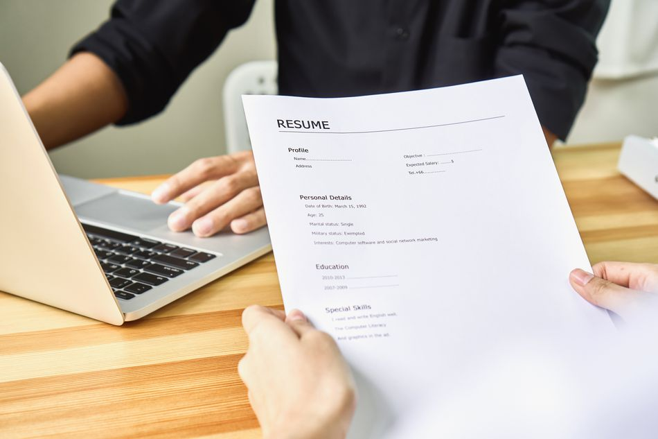 Person Holding Resume Against Business Person Using Laptop At Table