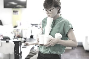 Unpaid intern carrying coffee cups to office workers.