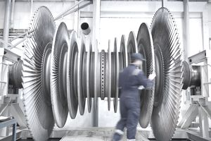 Engineer inspecting steam turbine blades in repair bay of workshop