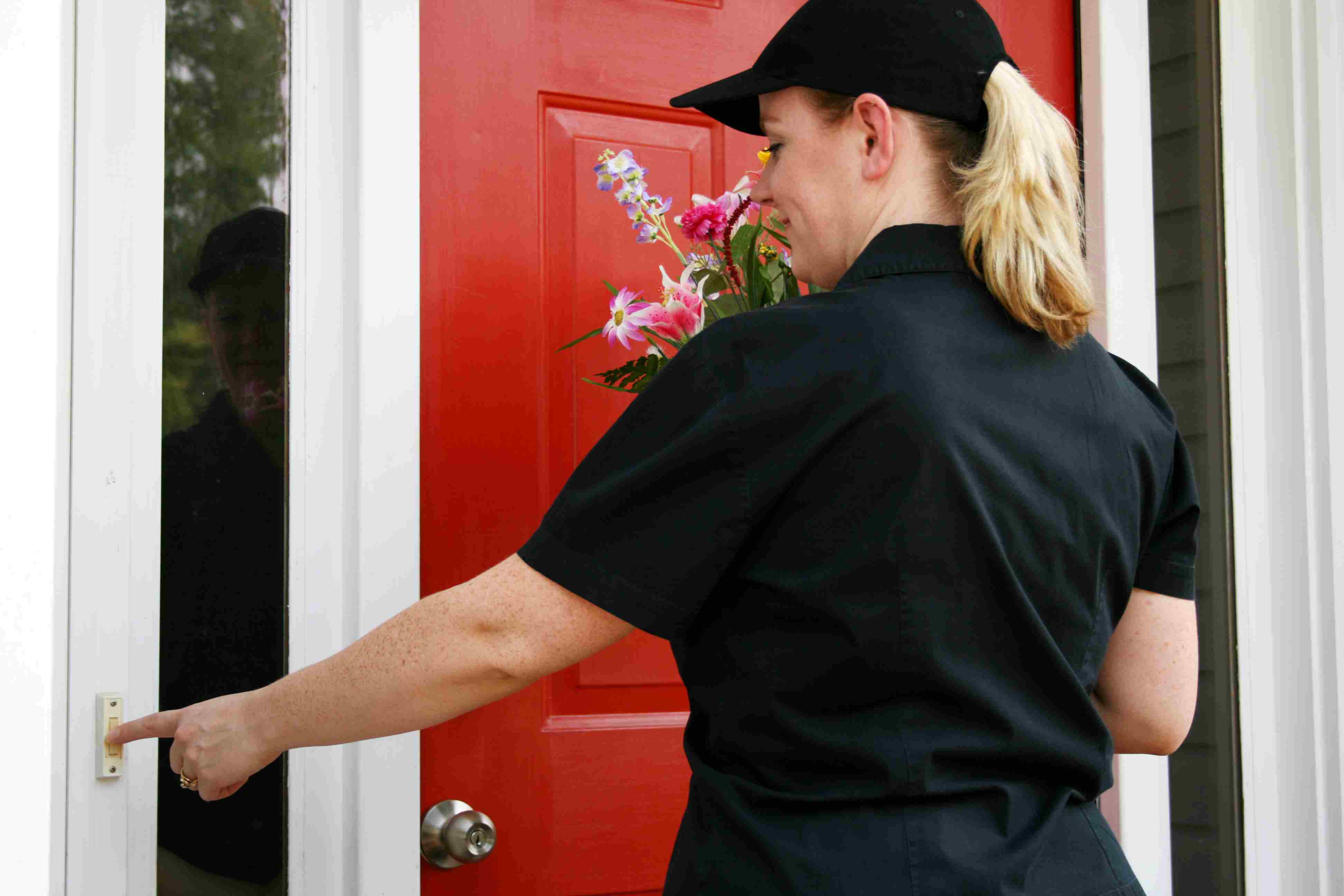 Female flower delivery person ringing doorbell with floral delivery