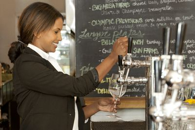 bartender pouring a beverage during her shift as a seasonal employment at a restaurant.