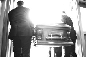 Two pallbearers carrying a casket