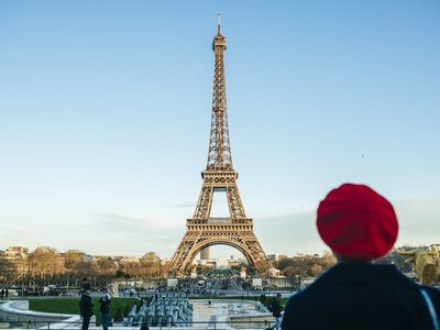 France, Paris, view to Eiffel Tower with back view of young woman standing in the foreground