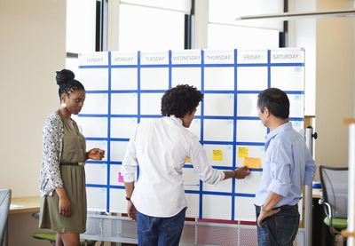 Three Office Workers Using a Large Calendar to plan projects