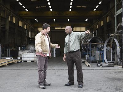 Factory manager and worker arguing in front of warehouse