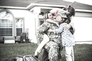 Soldier returning home on a compassionate assignment hugging his family in the front yard